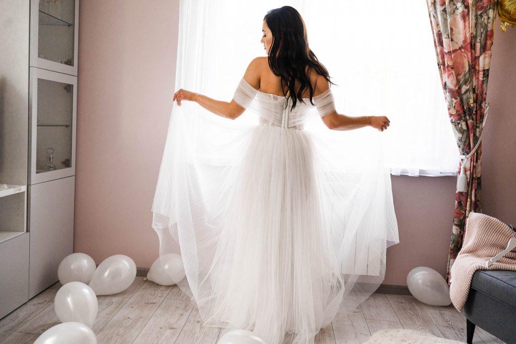 pani młoda suknia ślubna przy oknie