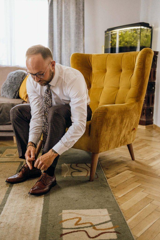 przygotowania ślubne dom pana młodego pan młody ubierający buty